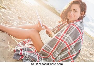 Woman covered with blanket using tablet PC at beach - Side...