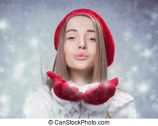 Happy beautiful young woman blowing snowflakes from her hands