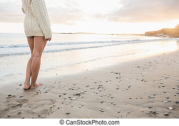 Low section of a woman in sweater standing on beach - Low...