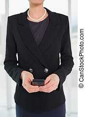 Mid section of businesswoman in suit holding a cellphone -...