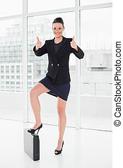 Elegant businesswoman with briefcase gesturing thumbs up -...