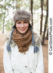 Woman wearing fur hat with woolen scarf and jacket in woods...