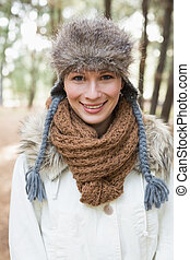 Portrait of a beautiful woman wearing fur hat with woolen scarf and jacket in the woods