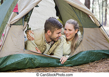 Loving couple lying in tent after a hike and looking at each...