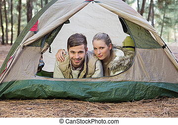 Happy couple lying in tent after a hike and looking at...