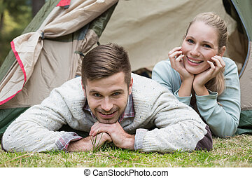 Young couple camping in the wilderness - Loving couple lying...