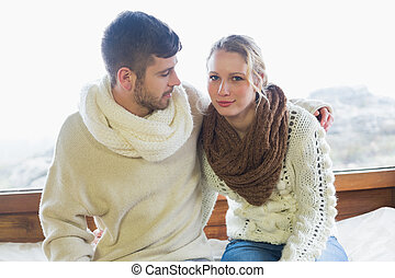 Couple in winter clothing sitting - Portrait of a young...