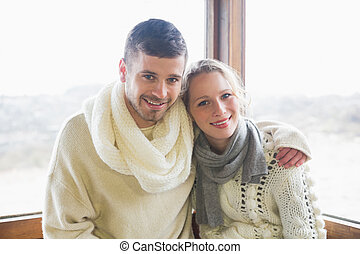 Couple in winter clothing sitting a - Portrait of a young...
