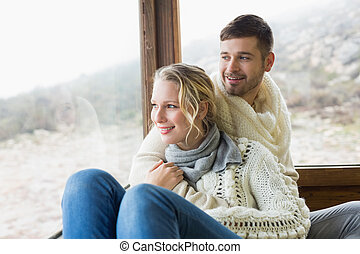 Couple in winter wear looking out through cabin window -...