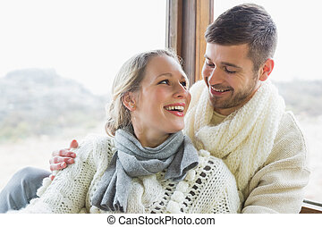 Cheerful young couple in winter clothing against cabin...