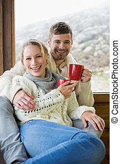 Cheerful couple in winter clothing holding cups against...