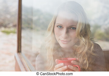 Content woman with coffee cup looking through window -...