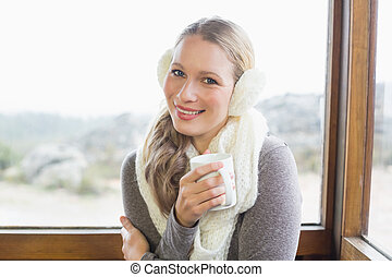 Smiling woman wearing earmuff with coffee cup against window...