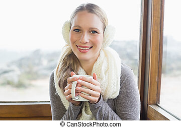 Portrait of a smiling young woman wearing earmuff with...