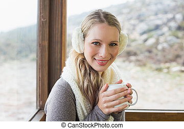 Woman wearing earmuff with cup against window - Portrait of...