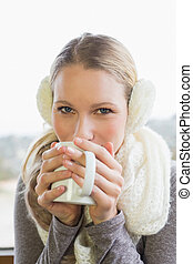 Woman wearing earmuff while drinking coffee - Close-up...