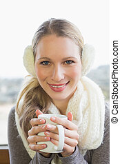 Smiling woman wearing earmuff with drinking coffee -...