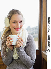 Smiling woman wearing earmuff with cup against window -...