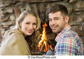 Smiling young couple in front of lit fireplace - Close-up...