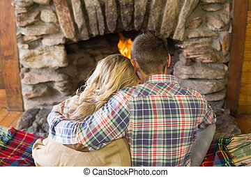 Romantic couple sitting in front of - Rear view of a...
