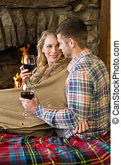 Romantic couple with wineglasses in front of lit fireplace