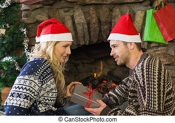 Man gifting woman in front of lit f