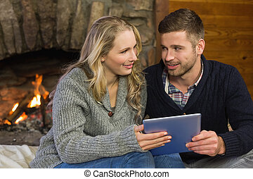 Couple using tablet PC in front of lit fireplace - Happy...