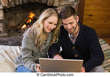Couple using laptop in front of lit - Smiling lovely young...