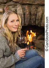 Beautiful woman with wineglass in front of lit fireplace -...