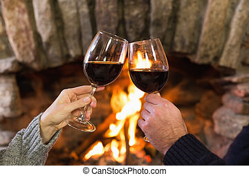 Hands toasting wineglasses in front of lit fireplace -...
