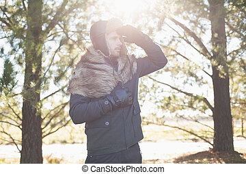 Young man in warm clothing looking away in forest on a...