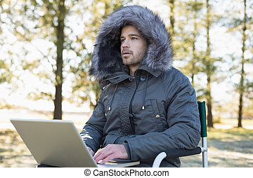 Young man in fur hood jacket using laptop in forest - Young...