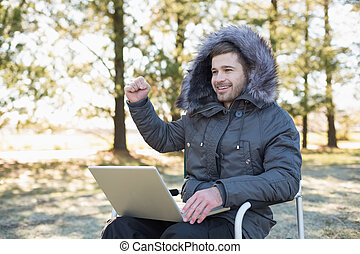 Cheerful man in fur hood jacket usi