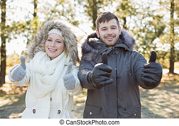 Couple in jackets gesturing thumbs up in the woods -...
