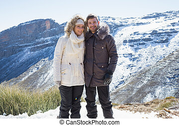 Portrait of a smiling young couple in fur hood jackets against snowed mountain range