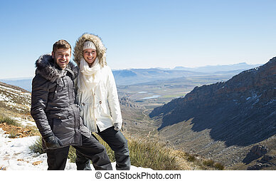 Couple in fur hood jackets against snowed mountainous valley
