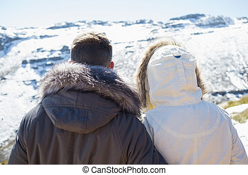 Couple in jackets looking at snowed
