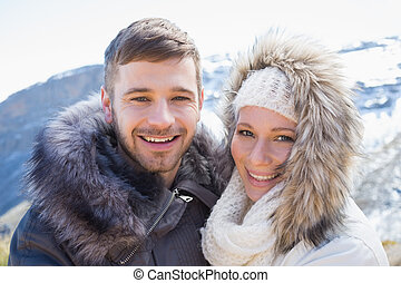 Loving couple in jackets against snowed mountain - Close-up...