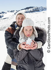 Couple with snow in hands on snowed landscape - Portrait of...