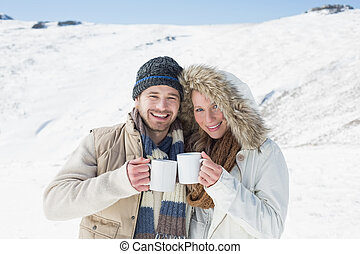 Portrait of a cheerful young couple in warm clothing with...