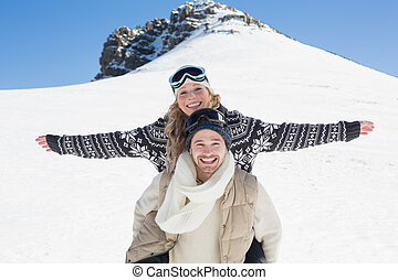 Wan piggybacking cheerful woman against snow covered hill -...