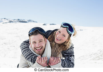 Cheerful couple with ski goggles on snow - Close-up portrait...