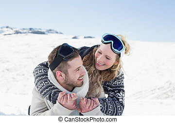 Close-up of a cheerful couple with ski goggles on snow -...