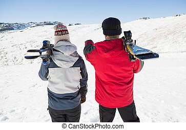 Rear view of a couple with ski boards on snow - Rear view of...