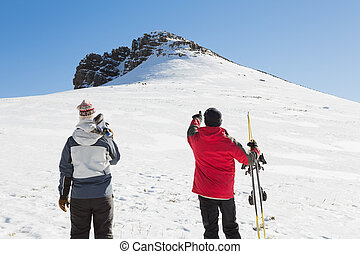 Rear view of a couple with ski boards standing on snow...