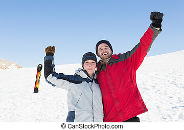 Couple raising hands with ski board on snow in background