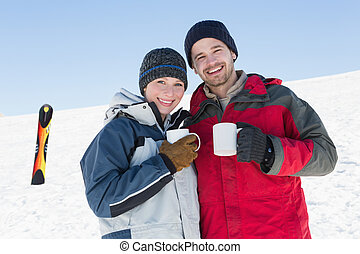 Couple having coffee with ski board in snow - Happy loving...