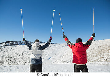 Rear view of a couple raising ski poles on snow covered...