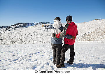 Full length rear view of a couple standing on snow covered...