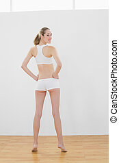 Rear view of beautiful slender woman posing in sports hall...